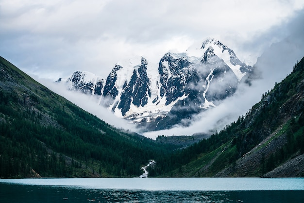 Красивый большой ледник, скалистые снежные горы, хвойный лес на холмах, горное озеро и горный ручей под облачным небом.