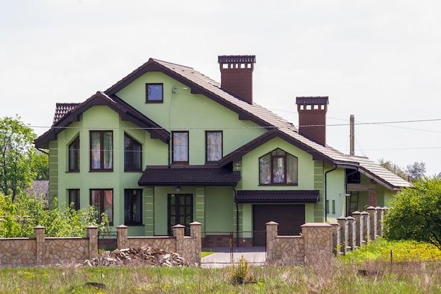 Beautiful big luxurious green brick house with garage, paved driveway, two chimneys, tiled roof and stone fence among green trees in quiet neighborhood. modern architecture and real estate concept.