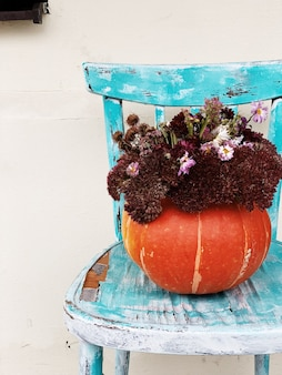 A beautiful big orange pumpkin with floral composition lying on old blue chair