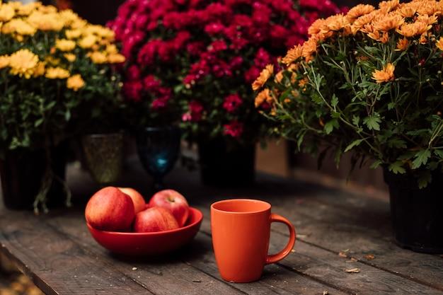 美しい大きな赤いリンゴは、木製のテーブルの赤いカップの横にある赤いプレートに横たわっています