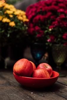 美しい大きな赤いリンゴは、木製のテーブルの赤いプレートに横たわっています