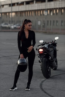 A beautiful biker woman holding helmet next superbike outside a building.