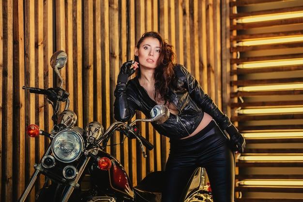 革のジャケットと革のズボンの美しいバイカーの女性は、彼のオートバイの隣に立っています。