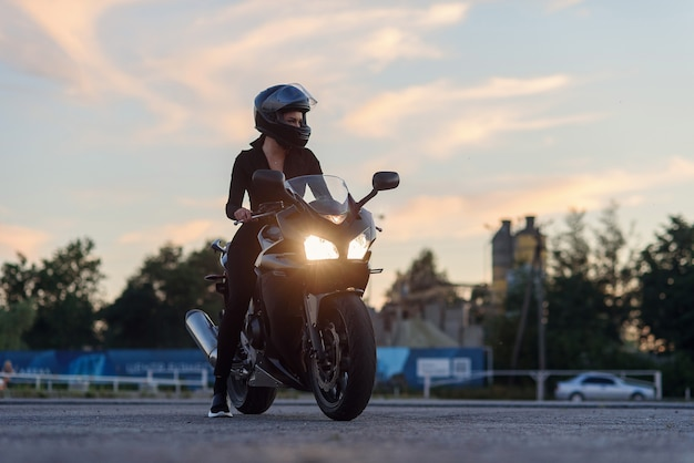 A beautiful biker woman leaning on her superbike outside a building.