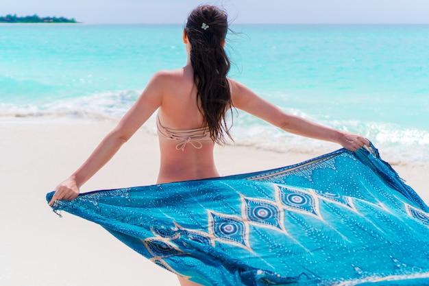 海の夕日に流れるカバーアップビーチウェアファッションラップでリラックスした美しいビキニ体の女性。