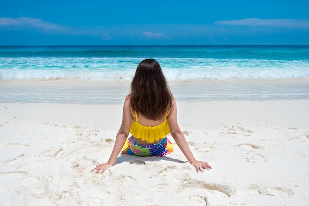 Beautiful bikini woman sit and looking sky on tropical beach nature with white sand and blue sea