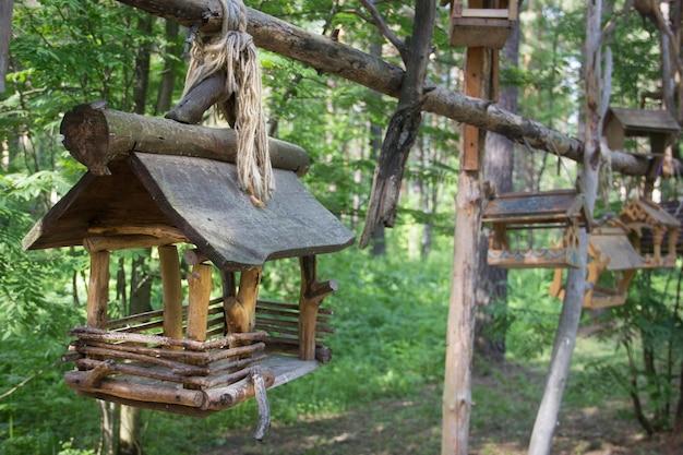 Красивая кормушка для птиц в парке. деревянный домик для птиц на дереве