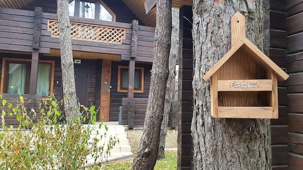 갈색 컨트리 목조 주택 근처 숲에서 나무로 만든 아름다운 새집. 집에서 만든 새 모이통. 정원에 있는 나무에 있는 예술 새집.