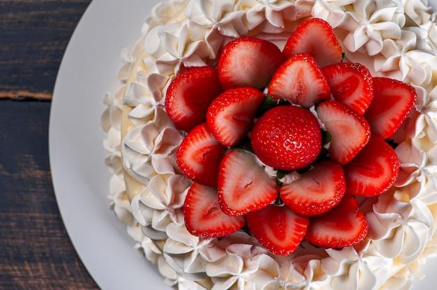 Красивый праздничный торт, покрытый шантильи и свежей клубникой. вид сверху