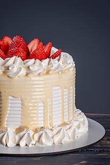 Beautiful birthday cake covered with chantillly and fresh strawberry. grey background. copy space