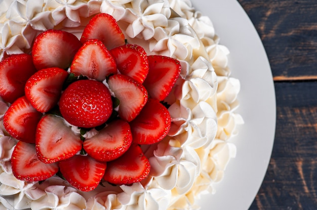 Beautiful birthday cake covered with chantillly and fresh strawberry. top view