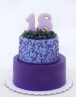 천연 블루 베리와 함께 숫자 18과 라일락 톤의 아름다운 생일 케이크