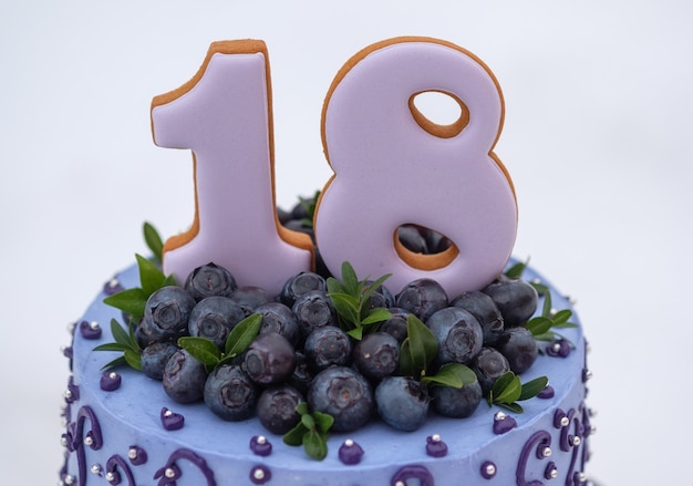 Beautiful birthday cake in lilac tones with the number eighteen with natural blueberries