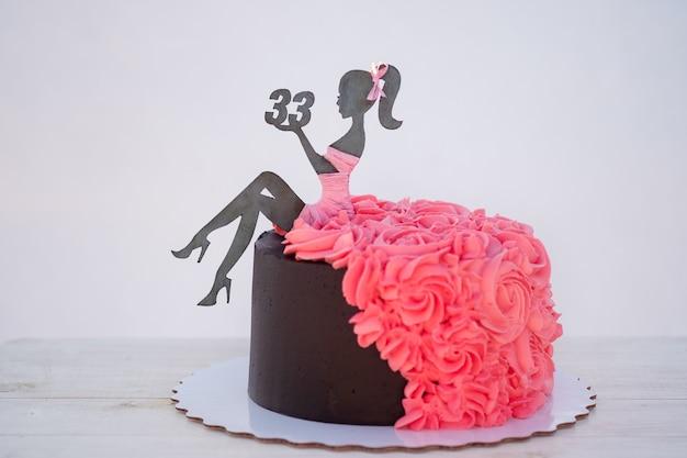 ピンクのクリームで飾られた、女性の姿と33番の美しいバースデーケーキ