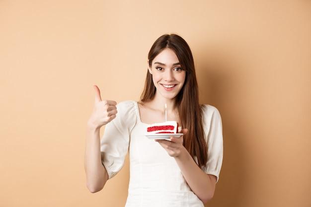ケーキに願い事をし、親指を立てて幸せそうに笑って、b-dayパーティーを楽しんで、ベージュの上に立っている美しい誕生日の女の子。