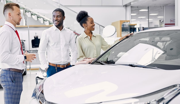 Beautiful black afro couple attentively listen to consultant in dealership