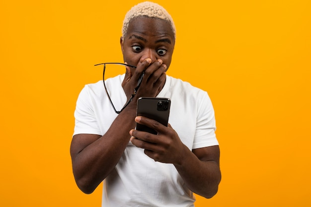 Beautiful black american student with white hair looks in surprise on the phone and covers his mouth with his hand