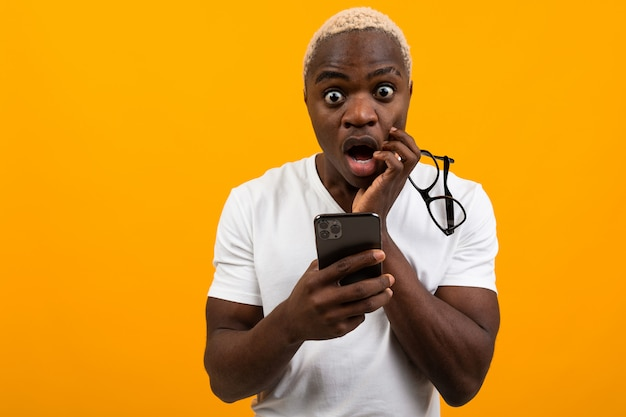 Beautiful black american student with white hair looks in surprise on the phone on a yellow studio background