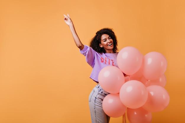 생일 파티를 준비하는 아름 다운 흑인 여성 모델. 이벤트 후 미소로 춤추는 보라색 셔츠에 세련된 아프리카 소녀.