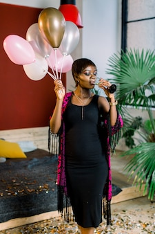 Beautiful black female model with balloons and a glass of champagne preparing for birthday party. refined african girl in black dress staying with smile after event.
