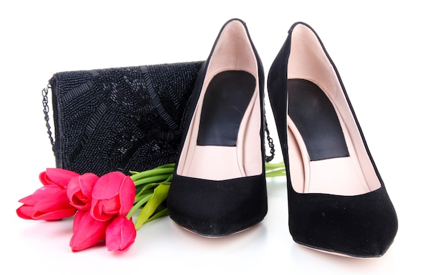 Beautiful black female shoes, bag and flowers, isolated on white