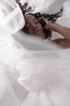 白いカーテンの後ろでポーズをとる絹のようなドレスを着た美しい黒人の女の子。