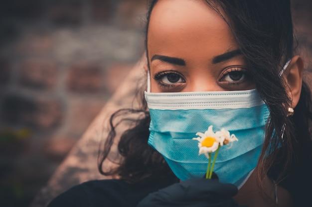 Bella ragazza nera all'aperto con una mascherina medica