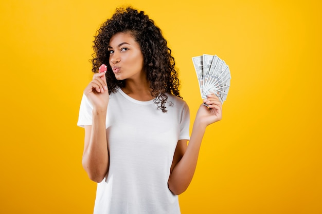 Beautiful black girl with poker chip from online casino and dollars money isolated over yellow
