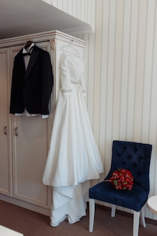 Beautiful black grooms jacket and brides dress hanging in hotel room
