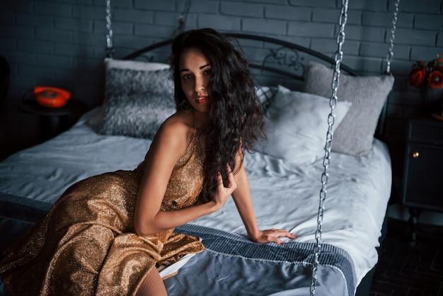 美しい黒髪。高級アパートの鎖の白いベッドに座っている黄金のドレスの女の子