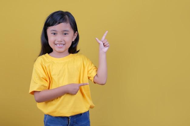 검지 손가락으로 가리키는 노란색 티셔츠에 아름 다운 검은 머리 소녀