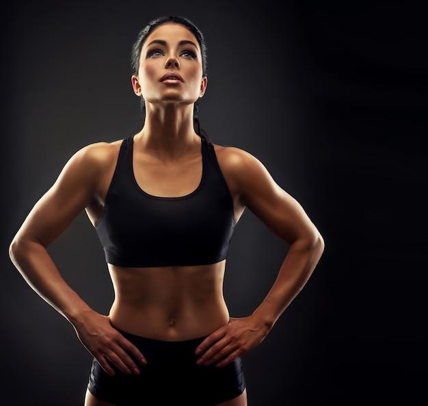 スポーツ服を着た形の良い体を持つ美しい黒髪の女性は、彼女のよく訓練された体を示しているスポーティな女性の上を見上げていますフィットネス、スポーツトレーニング、健康的なライフスタイル