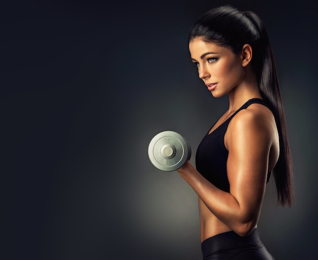 Beautiful black haired woman with well shaped body is lifting a dumbbells, sporty woman showing her well trained body fitness, sport training and healthy lifestyle
