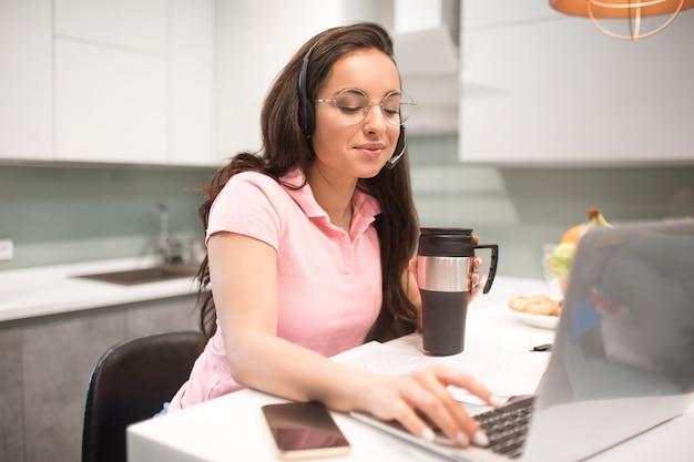 美しい黒髪の女性は自宅で動作します。従業員が台所に座っています。