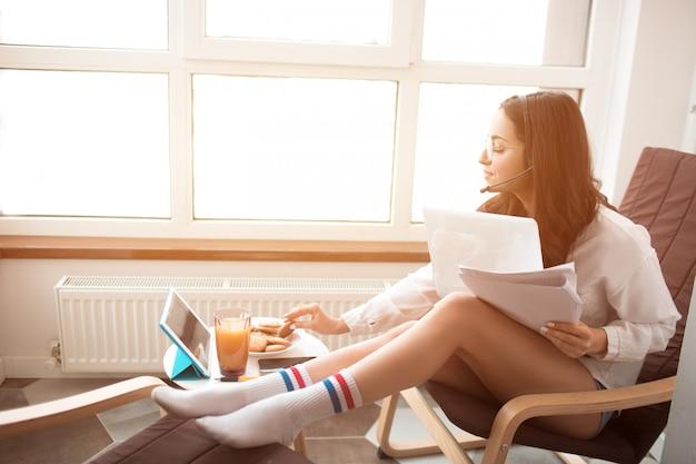 美しい黒髪の女性は自宅で仕事をし、ヘッドセット付きのヘッドフォンを使用しています。