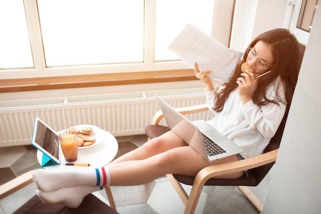美しい黒髪の女性は自宅で仕事をし、ヘッドセット付きのヘッドホンを使用しています。