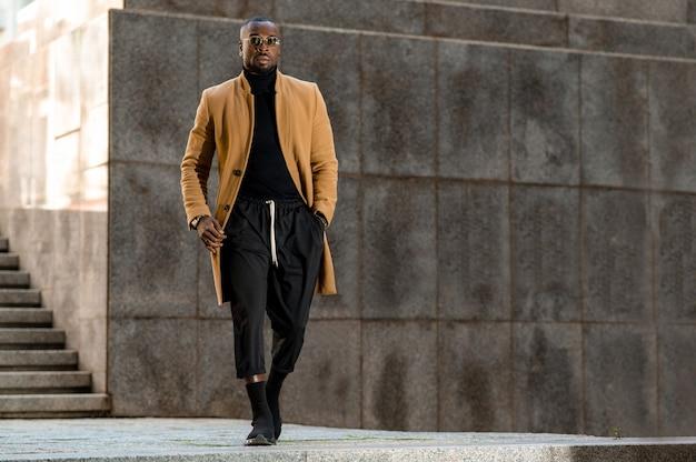 Красивый темнокожий мужчина в элегантной одежде, ходьба с руками в кармане. городской образ жизни.