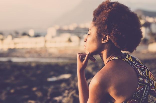 Красивая черная раса африканская модель молодая женщина остается сидеть и думать о побережье на берегу океана
