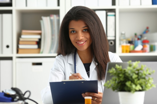 Beautiful black smiling female doctor holding a clipboard