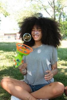 シャボン玉で遊ぶ美しい黒人の10代の少女