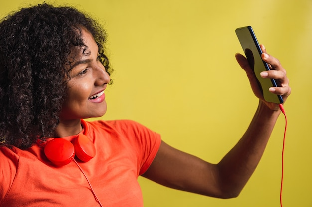 Beautiful black teenage girl with afro curls hairstyle takes a selfie on yellow background.