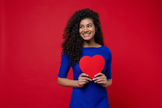Beautiful black woman in blue dress with heart shaped valentine card on red wall