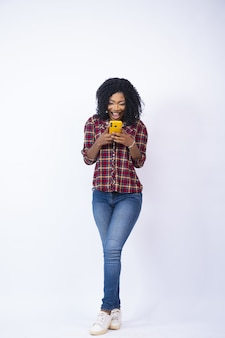 Beautiful black woman excitedly looking at her phone