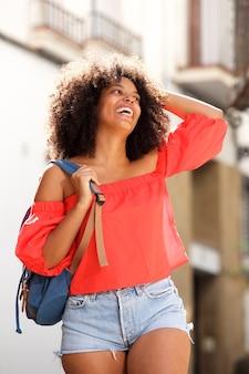 Красивая черная женщина смеется снаружи с рюкзаком