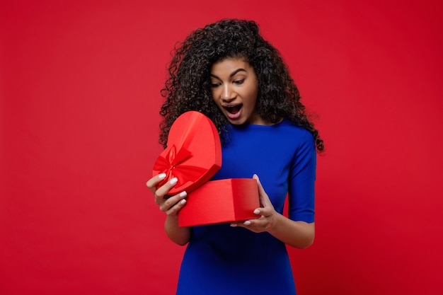 Beautiful black woman opening heart shaped valentine gift box on red wall