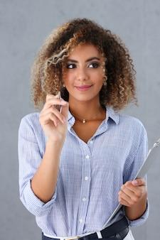 아름 다운 흑인 여성 초상화입니다. 손에 볼펜을 들고 패션 유행 스타일의 곱슬 머리를 가리 킵니다.