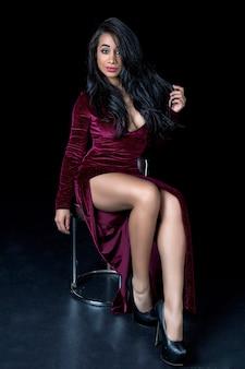 広いネックラインで示唆に富むバーガンディのドレスに座って服を着た美しい黒人女性