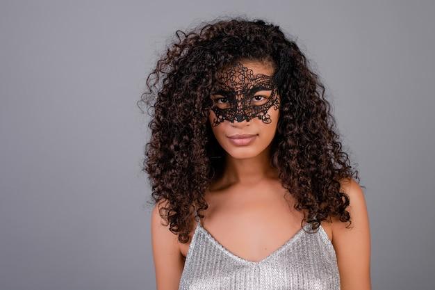 Beautiful black woman wearing elegant masquerade mask isolated over grey