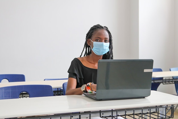 Beautiful black woman wearing a mask and studying at a computer