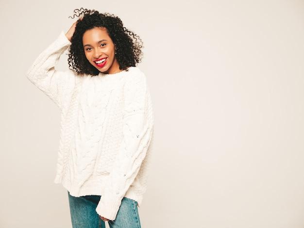 アフロカールの髪型と赤い唇を持つ美しい黒人女性。流行のジーンズの服と冬のセーターの笑顔モデル。
